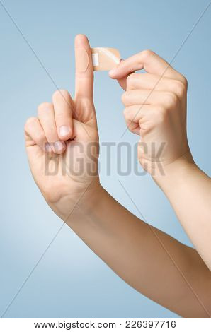 Woman Putting A Plaster On Her Index Finger