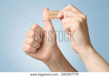 Woman Putting A Plaster On Her Thumb
