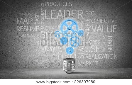Glass Lightbulb With Multiple Gears Inside Placed Against Business Related Terms On Grey Wall On Bac