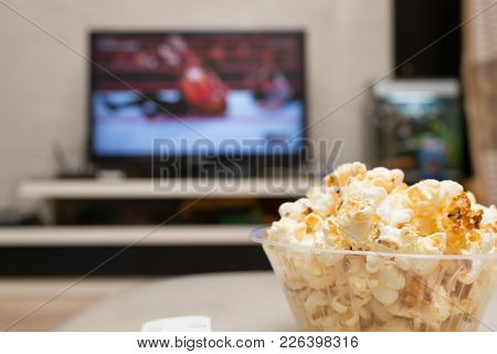 Popcorn And Remote Control On Sofa With A Tv Broadcasting Wrestling On Background