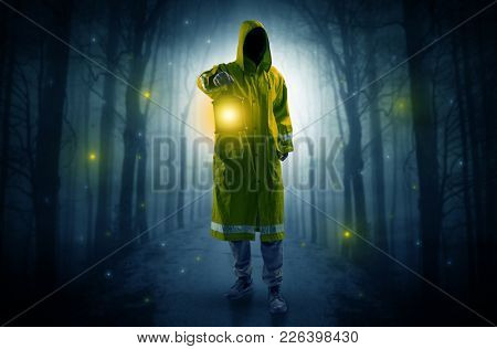 Man in raincoat coming from dark forest with glowing lantern in his hand concept