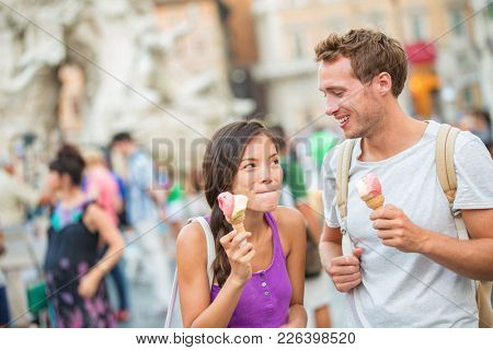 Ice cream summer fun couple eating gelato in Rome on Piazza Navona. Happy people having fun eating ice cream on vacation travel in Italy, Europe. Young funny girl licking lips of italian food outdoor.