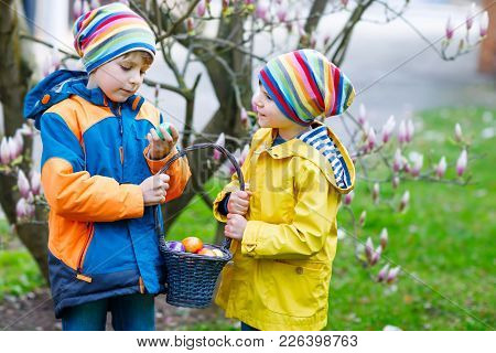 Two Little Kids Boys And Friends Making Traditional Easter Egg Hunt In Spring Garden, Outdoors. Sibl