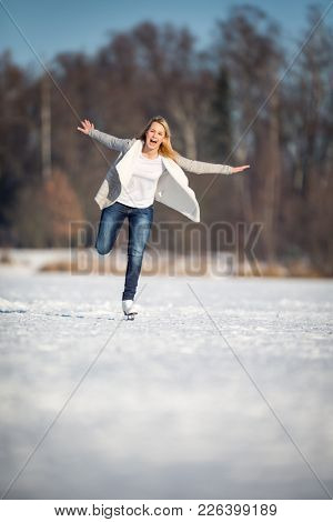 Young woman ice skating outdoors on a pond on a freezing winter day (color toned image; motion blurred image)