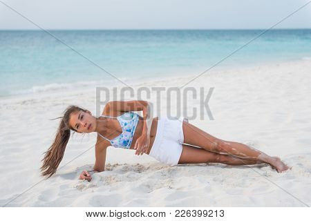 Planking exercise side plank with twist yoga fitness girl training obliques muscles for stomach toning on sunset beach. Active woman travel lifestyle.