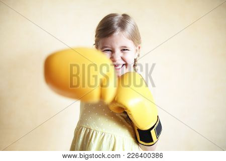 Little Girl With Yellow Boxing Gloves Over Yellow Wall Background. Girl Power Concept. Funny Little
