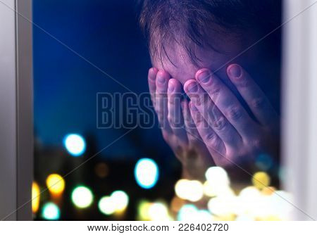 Sad Man Crying Late At Night By A Window. Depressed Person Covering Face. Having Headache Or Eye Dis