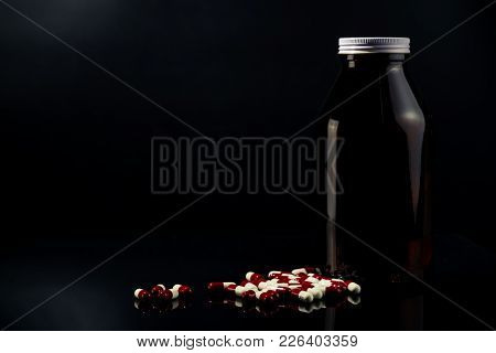 Red, White Antimicrobial Capsule Pills And Amber Glass Bottle On Dark Background With Blank Label An