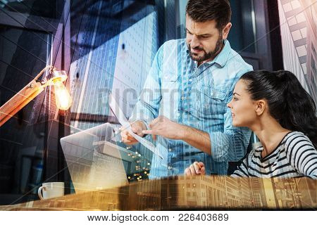 Giving Instructions. Calm Smart Reliable Employer Standing In Front Of A Laptop And Showing A List O