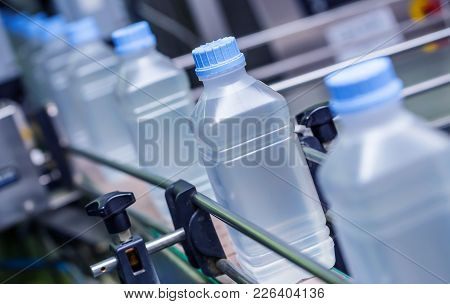 Saline Bottle Filling In Pharmaceutical Manufacturing. Saline Bottle Being Filled Up On Assembly Lin