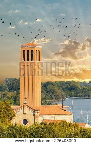 Bell Tower On Coast Of Venice At Sunrise With Flock Of Birds