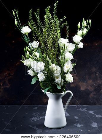 Elegant Flowers Bouquet With White Lisianthus And Decorative Green Stems In White Tin Jug Closeup On