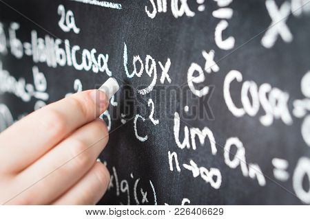 Professor Writing Mathematical Formula And Equation To Blackboard In School Classroom. College Or Un