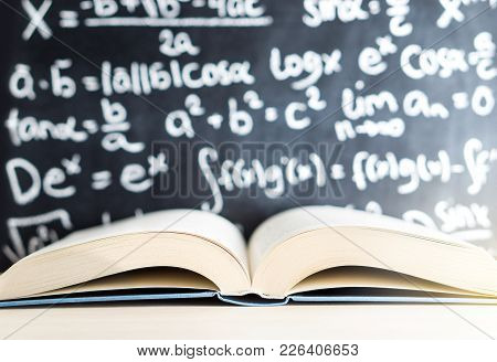 Knowledge, Education, Mathematics, Science And Wisdom Concept. Open Book In Front Of A Blackboard An