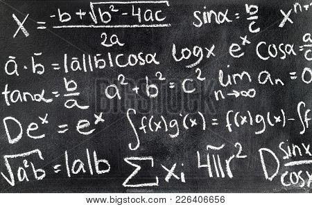 Handwritten Mathematical Formulas On Blackboard Written With Chalk. Chalkboard Full Of Theory And Ca