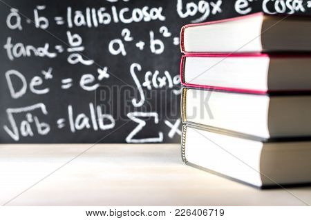 Stack And Pile Of Books In Front Of A Blackboard In School. Math Equation Written On Chalkboard.