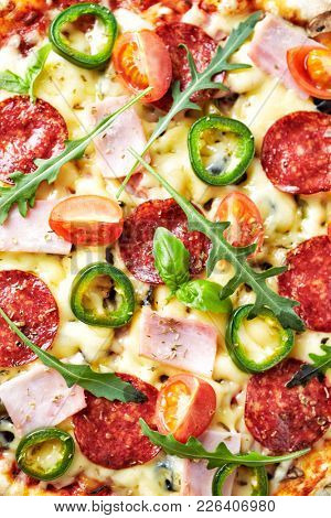 Pizza with Salami, Ham, Cherry Tomatoes and jalapeno Pepper