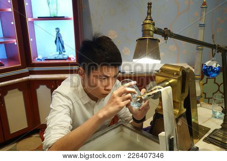 Shanghai, China- Jan 22, 2018: Young Crafsman Concentrate On A Glass Crafting On A Cup.