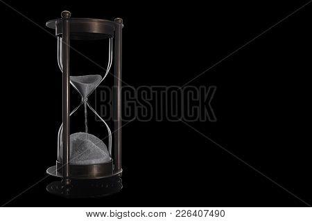 Elegant And Stylish Bronze Vintage Sandglass With Trickling White Sand. Isolated On Black Background