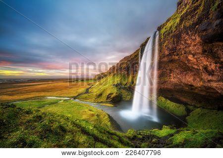Seljalandsfoss Waterfall  In Iceland At Sunset. Long Exposure.