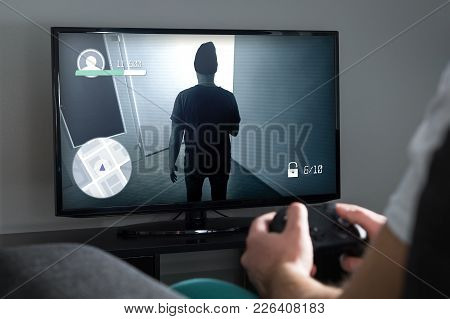 Playing Video Games At Home With Console. Gamer With Controller Or Gamepad In Hand. Young Man And Tv