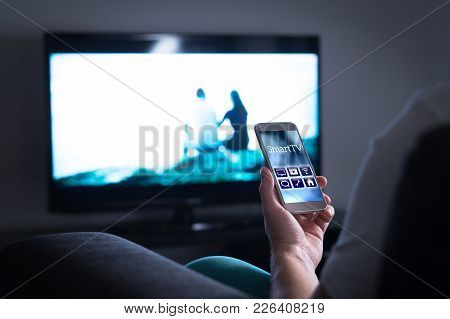 Man Watching Television And Using Smart Tv Remote Control Application On Mobile Phone. Choosing Movi