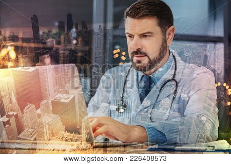 Looking Interested. Calm Concentrated Smart Doctor Feeling Interested While Sitting In Front Of A La