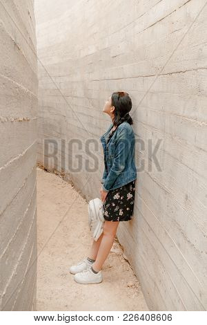 Attractive Young Woman Stands Between Concrete Walls. Caucasian Girl In Casual Jeans And Flower Dres