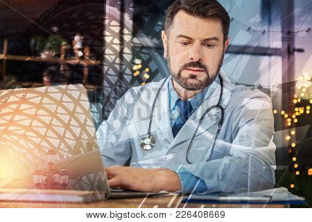 Necessary Information. Calm Concentrated Experienced Doctor Sitting In Front Of A Modern Laptop And