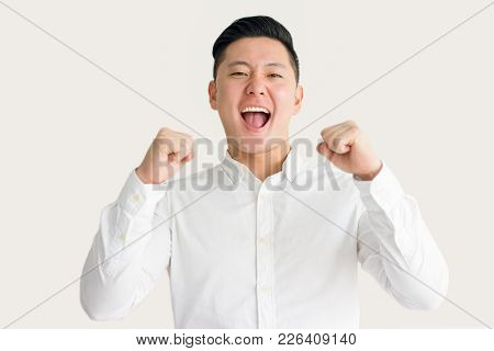 Excited Asian Man In White Shirt Celebrating Success With Fists Up. Young Businessman Showing Winnin