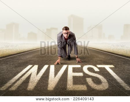 Young determined businessman kneeling before invest sign