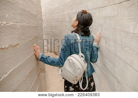 Attractive Young Woman Standing Between Concrete Walls. Caucasian Girl In Casual Jeans And Flower Dr