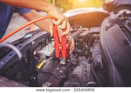 Close Up Of Auto Mechanic Jumping Battery Car,check Voltage Level Car Battery,helping Concept.