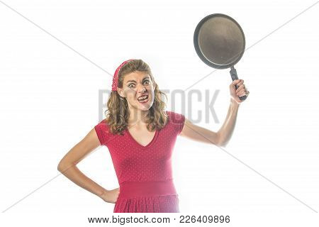 Angry Woman In Red Vintage Dress Waving With A Frying Pan, Swinging With It, Studio Image