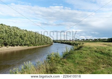 View Of The River Bank, Wood And Sky