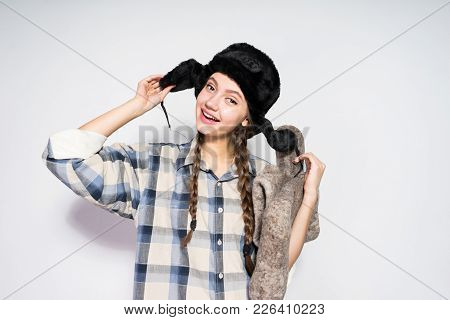 Happy Young Russian Girl In A Hat With Ear-flaps Holds Gray Felt Boots In Hands