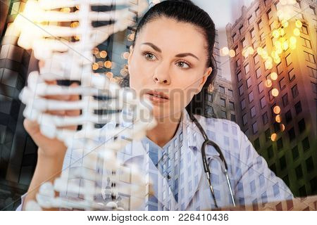 Genetic Research. Calm Clever Enthusiastic Doctor Looking Interested While Sitting With A Phonendosc