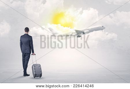 Young businessman with luggage walking towards to a raising airplane