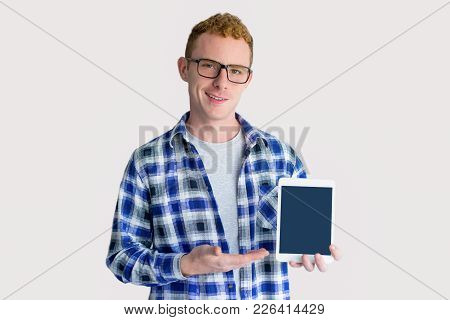 Smiling Red Haired Young Caucasian Man Wearing Glasses And Checked Shirt Showing Tablet With Empty S