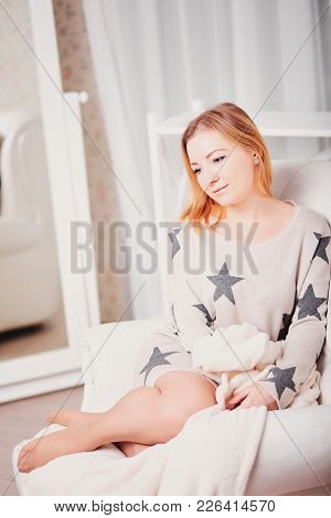 Beautiful Young Woman Sits With Her Head Tilted And Looking Down. Portrait Of A Pretty Girl In A Lig