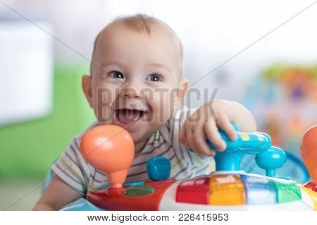 Funny Smiling Baby Boy Playing In Baby Jumper
