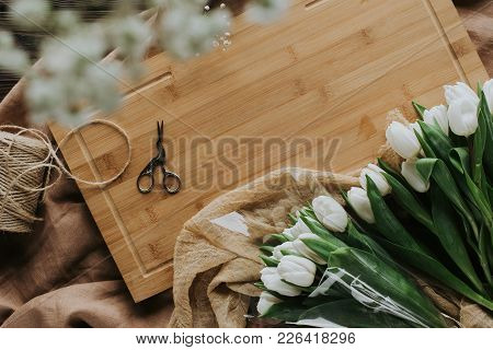 Top View Of White Tulips, Scissors And Twine On Wooden Board For 8 March