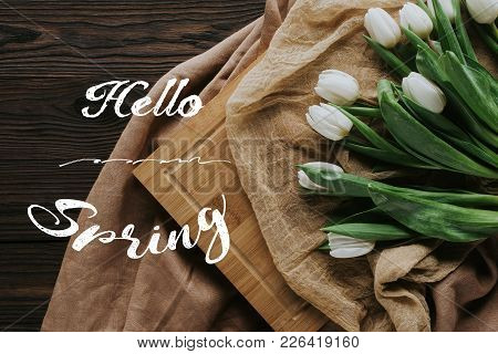 Top View Of Spring Tulips On Tablecloth And Wooden Board With Hello Spring Lettering