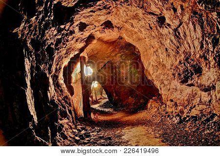 Into The Unknown. Winding Illuminated Path Through An Underground Mine Shaft