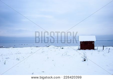 Old Fishing Cabin In A Snowy Coastal View At The Swedish Island Oland In The Baltic Sea