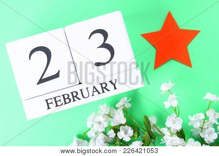 White Wooden Perpetual Calendar With The Date Of February 23 On A Green Background. Defender Of The