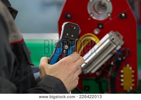 Electrician With Stripper Installing Energy System On Machinery Industry, Close Up