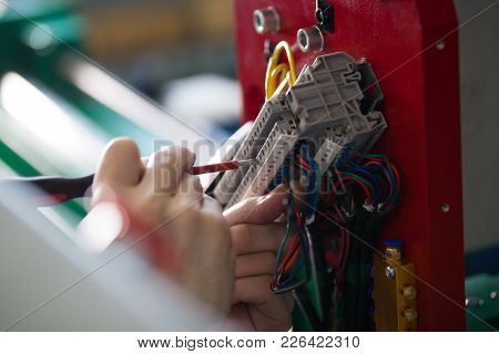 Hands Of Electrician Engineer Screwing And Testing Equipment In Fuse Box, Close Up
