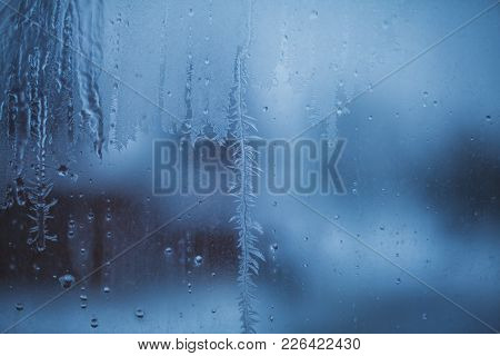 Moody Picture Of Water Drops Freezing On A Dirty Window Glass In Winter In Blueish Evening Light.
