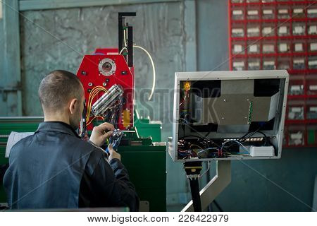 Man Worker Electrician Works With Energy Panel And Machinery Equipment On Plant, Rear View